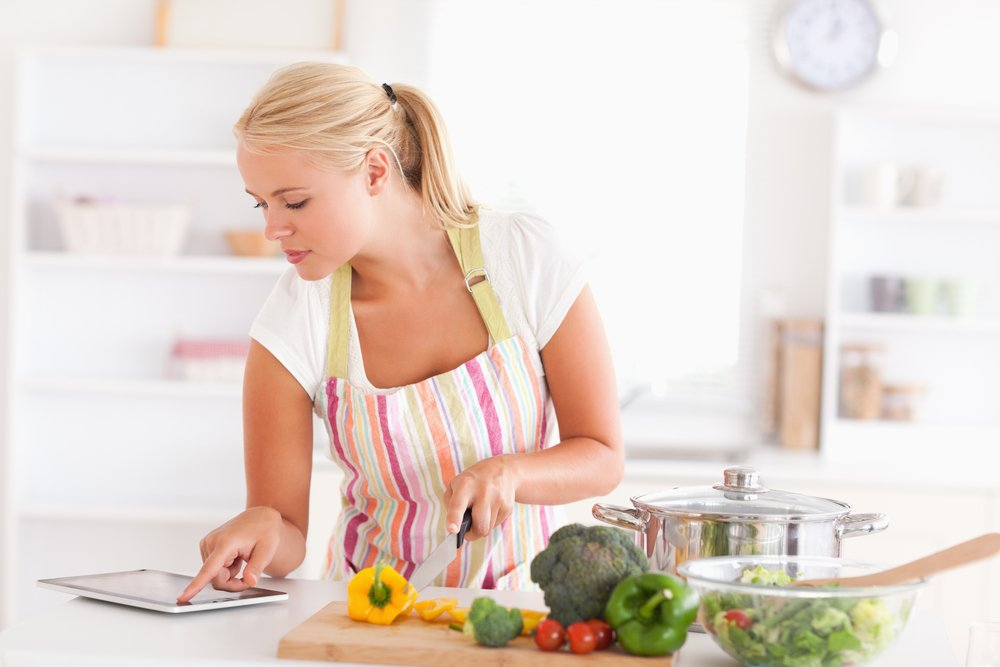 Blonde woman using a tablet computer to cook in her kitchen