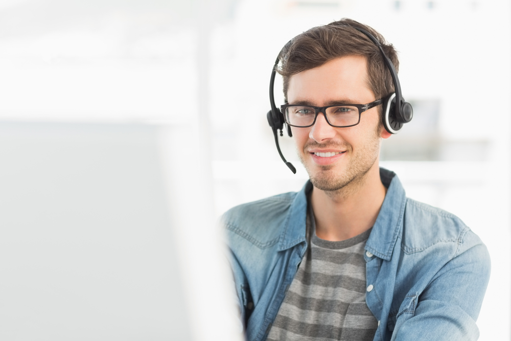 Smiling casual young man with headset using computer in a bright office